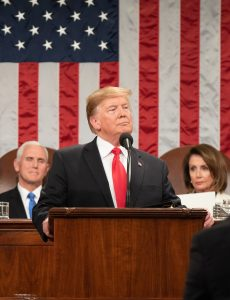President Donald Trump with Vice President Mike Pence and Speaker of the House Nancy Pelosi in the background.